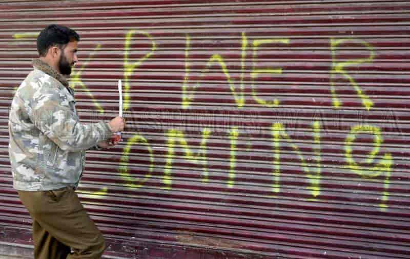 A policeman defacing the graffiti by painting it. Photograph by Shahid Tantray