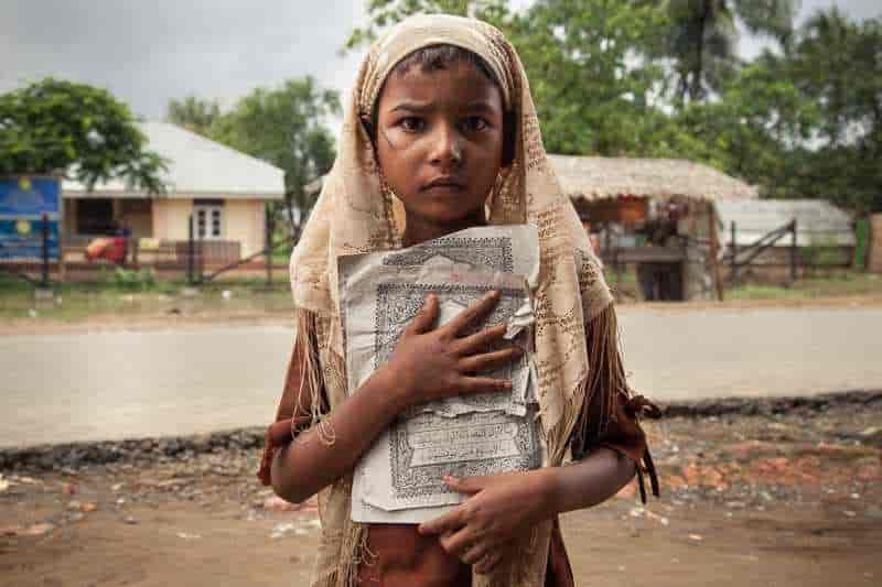 Sadiyah, 5, Boomay, holds broken pages of the Qu'ran as she walks home from a make-shift Madrasa set up in Thawepen unregistered IDP Camp, in the outskirts of Sittwe.