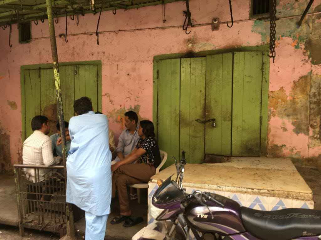 Meat sellers sit and chat outside a closed meat shop in Kotla Bazaar, Meerut.